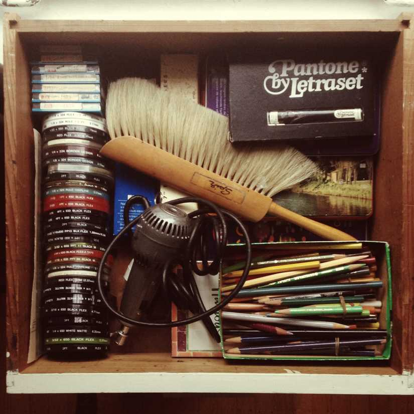 Drawer full of calligraphy and art supplies including pencil crayons, electric eraser, brush, and border tape