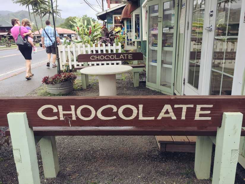 "Benches at the front of a small building with ""chocolate"" painted across the top"