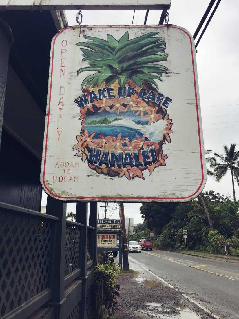 "A hanging sign with a detailed painting of a pineapple with a ocean and landscape scene in the centre. The words ""Wake up Cafe Hanalei"" are incorporated in the illustration."