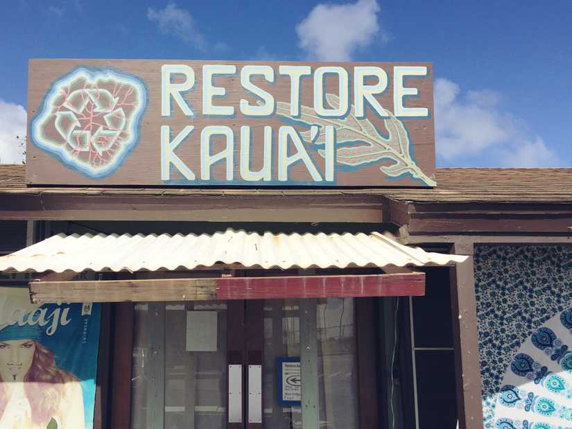 "A sign mounted to the roof of a shop that reads ""Restore Kaua'i"""