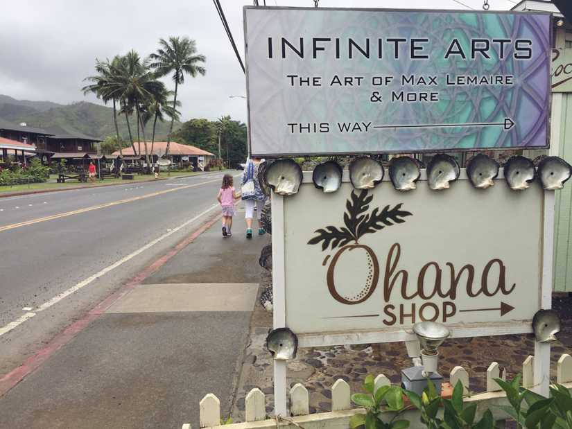 "A printed sign right above a beautiful hand painted script sign reading ""Ohana shop"""