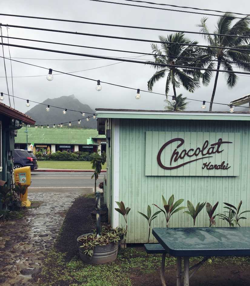 "A small building and courtyard with string lights above. The sign is cut from wood and reads ""Chocolate Hanalei"""