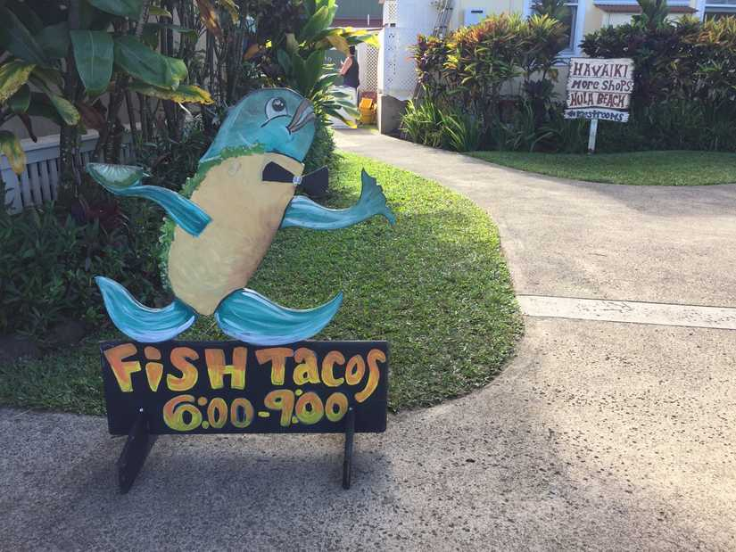 "A wood cut out sign that has a fish server and reads ""Fish Tacos"" below"
