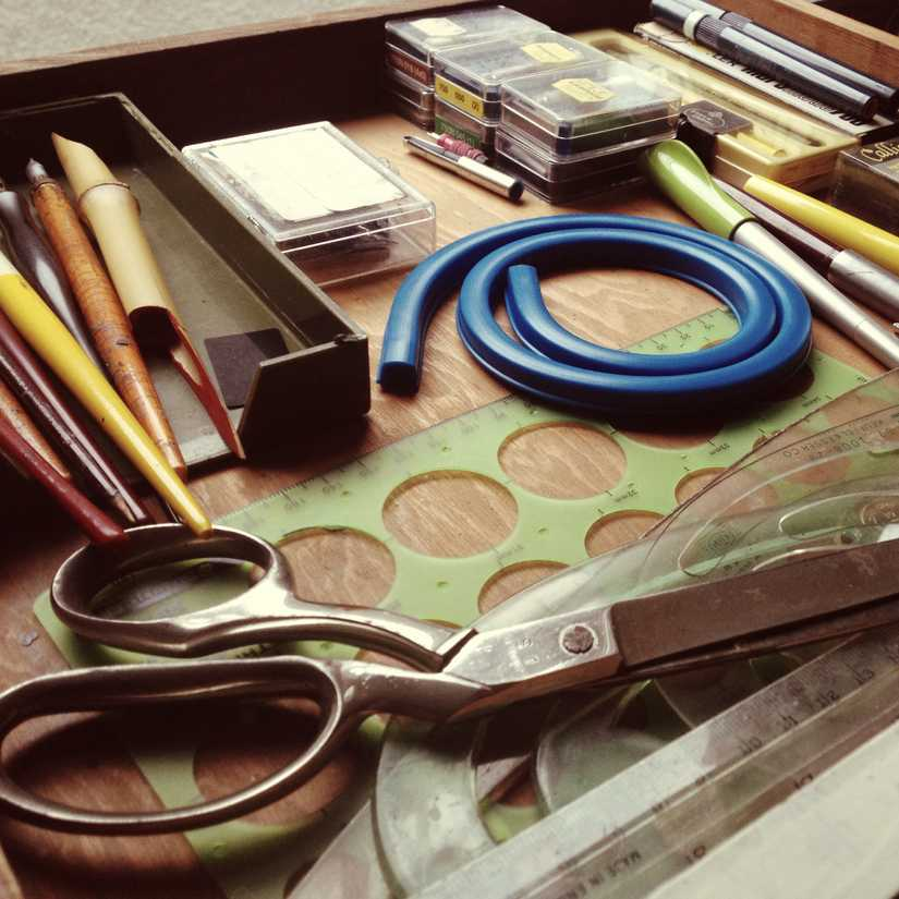 Drawer full of calligraphy and art supplies including pens, nibs, rulers, and scissors