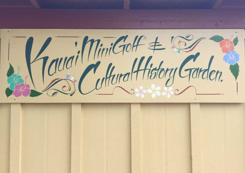 "Sign mounted to the side of a shed reading ""Kauai Mini Golf & Cultural History Garden"""